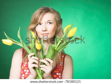 Portrait of young woman with yellow tulips #78180121