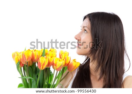Portrait of young woman with yellow tulips bouquet of flowers smiling and looking up isolated on white background