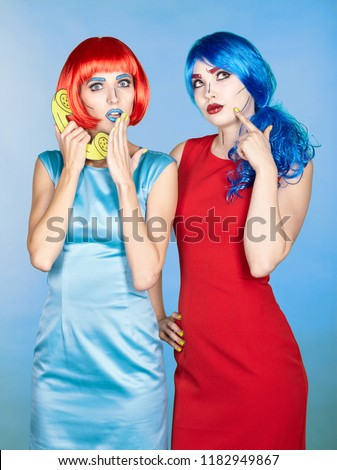 Portrait of young women in comic pop art make-up style. Females in red and blue wigs and dresses call on the phone