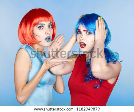 Portrait of young women in comic pop art make-up style. Shocked females in red and blue wigs and dresses.