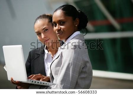 Portrait of young women in suit in front of a laptop computer