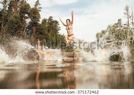 Portrait of young women jumping into a wilderness lake from the jetty. Young girl jumping from a pier at the lake