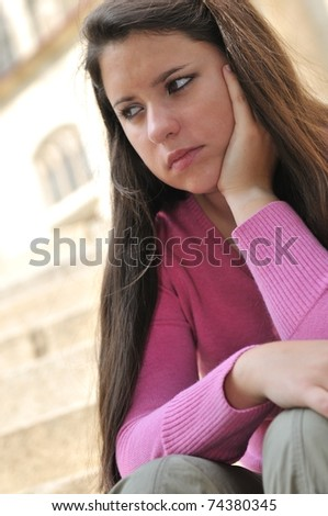 Portrait of young worried woman (teenage girl) in depression outdoors