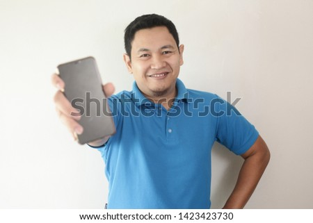 Portrait of young young Asian man presenting smart phone mockup with selective focus