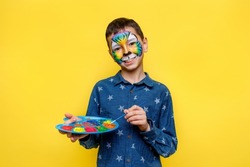 Portrait oh little  boy in casual shirt with aquagrim on face, colorful tiger with gouache palette isolated on yellow background.