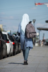 Portrait on back view of Veiled Muslim woman walking in the street near the train station