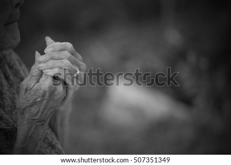 Portrait on Black Of Old woman Praying. #507351349