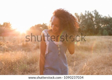 Stock Photo portrait outdoors of a beautiful happy young afro american woman smiling at sunset. Yellow background. Lifestyle in nature. Casual jean dress clothing