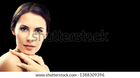 Portrait photo of beautiful young woman with naked shoulders, with empty copy space place for some text, advertising or slogan, over black background. Brunette model - beauty, glamour, fashion picture