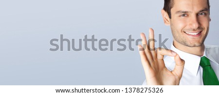 Portrait photo of confident businessman in green tie, showing okay gesture, with empty copy space wide place for some text, advertising or slogan, on grey background. Business concept picture.