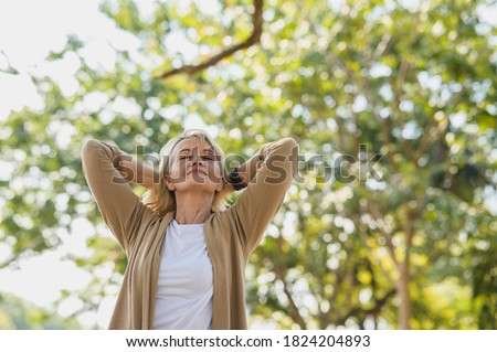 Portrait photo of happy senior Caucasian woman relaxing and breathing fresh air with sunlight in outdoors park. Elderly woman enjoying a day in the park on summer. Healthcare lifestyle and wellness
