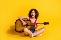 Portrait photo of hipster female musician with curly hair singing song holding keeping playing melody guitar chords smiling sitting down isolated on vivid yellow color background