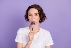 Portrait photo of hungry girl on diet licking spoon before dinner isolated on bright violet color background