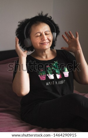 Portrait photo of mature woman curly hair listen music with headphone with smile