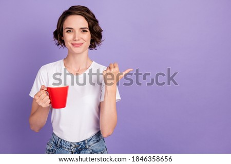 Portrait photo of nice cute girl holding cup of coffee showing at empty space smiling isolated on vivid violet color background