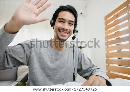 Portrait photo of smart Asian guy using video call communicate with business colleague friend from home during self isolation from coronavirus outbreak crisis. Asian man waving hand looking at camera.