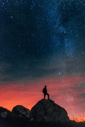 Portrait photo of the silhouette of a man standing on top of a rock with the milky way galaxy in a pinky night sky in the background. Shot in Triglav National Park, Slovenia.