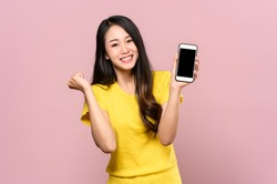 Portrait photo of young beautiful Asian woman feeling happy or surprise shock and holding smart phone with black empty screen on pink background can use for advertising or product presenting concept.