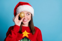 Portrait photo of young funny millennial girl wearing christmas headwear cap keeping holding golden sparkling ball bauble for decorating xmas tree looking at side isolated on blue color background