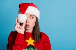 Portrait photo of young millennial girl wearing christmas cap keeping holding white soft cotton ball in hand looking at side with pouted plump lips sending air kiss isolated on blue color background