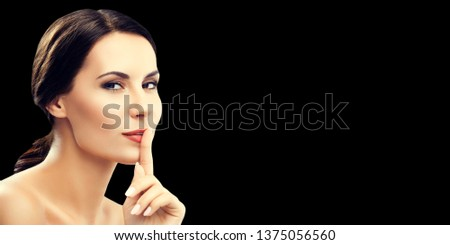 Portrait photo of young woman keeping finger on her lips and asking to keep quiet or secret, with copy space place for some text, advertising or slogan, on black background. Beauty concept picture.