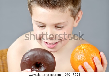 portrait photograph of a child with orange and donuts