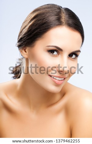 Portrait picture of beautiful smiling woman with naked shoulders, against grey background. Beauty concept photo.