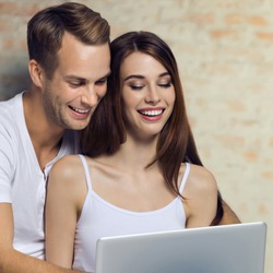 Portrait picture of happy smiling couple using laptop. Internet, shopping, online store, love, relationship concept, over loft style wall. Square composition image.