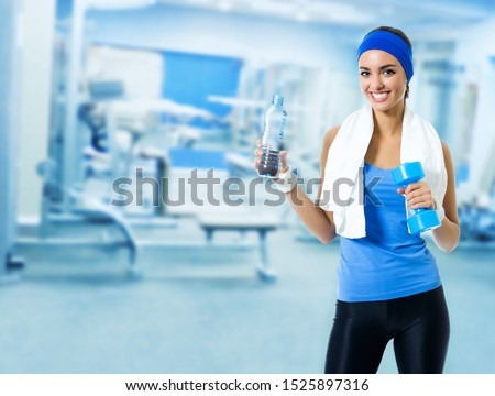 Portrait picture of happy smiling young brunette woman in fitness wear with bottle of water, at sport club or center, with copy space area for some slogan or text