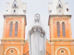Portrait picture of statue of Blessed Virgin Mary, Jesus's mother in front of old vintage brick church, the tourist attraction in Hanoi, Vietnam