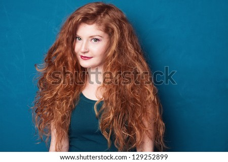 portrait picture of young beautiful ginger girl on blue background