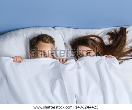 Portrait picture of young playfull couple peeping from bedsheet on the bed at bedroom. Caucasian models in love, relationship, dating, happy people, bedtime concept. #1496244425