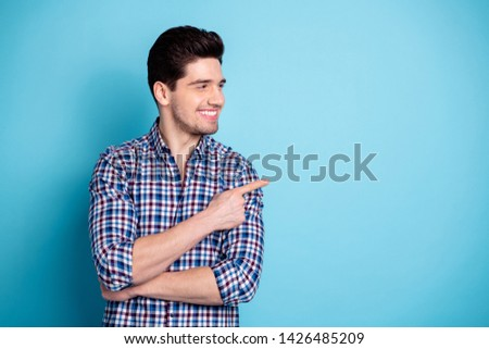 Portrait positive cheerful satisfied charming content cute person cute candid feedback adverts choose decide tip suggest option display look way  checkered clothing isolated blue background