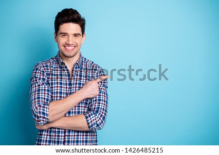 Portrait positive cheerful satisfied charming content pretty people  feedback adverts choose decide tip suggest pick option present display look information plaid outfit isolated blue background