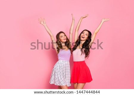 Portrait positive satisfied content rejoice millennial teen teenager weekend wavy curly long hairstyle hairdo raise stretch arms hands modern youth clothes isolated stylish trendy pink background