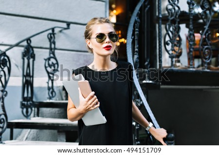 Portrait pretty businesswoman in black dress on stairs outdoor. She wears sunglasses, laptop, phone, looking to camera