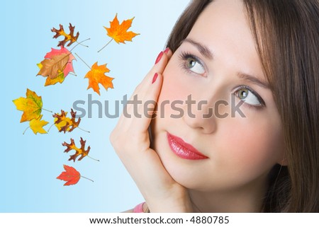 portrait pretty girl and autumn leaf on blue background
