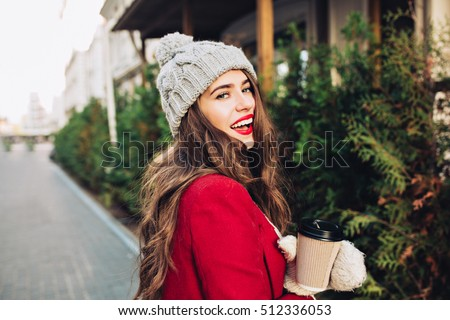 Portrait pretty girl with long hair in red coat walking on street with coffee to go. She looks excited to camera