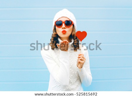 Portrait pretty woman blowing red lips sends air kiss holds lollipop heart wearing a heart shape sunglasses, knitted hat, sweater over blue background