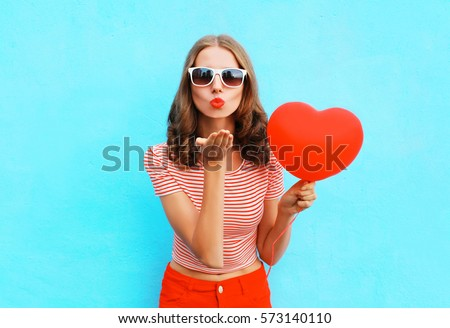 Portrait pretty woman sends air kiss with red balloon heart shape over blue background