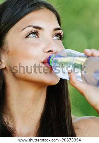 portrait pretty young woman background green summer park drinking water bottle