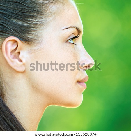 Portrait profile of face young beautiful woman, on green background summer nature.