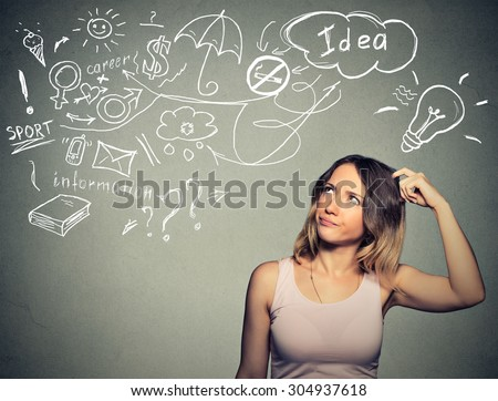 Portrait puzzled young woman thinking scratching head has many ideas looking up isolated gray wall background. Human face expression emotion feeling life perception. Decision making process concept