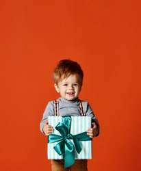 portrait red-haired toddler boy, 1.5 years old, holds a large gift box with a ribbon in front of him. happy holiday