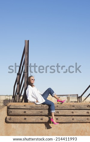 Portrait relaxed attractive mature woman sitting laid back in rural country area, wearing sunglasses, jeans and high heel shoes, with horizon and blue sky as background and copy space.