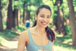 Portrait running young woman. Female runner jogging during outdoor workout in park on spring summer day. Beautiful fit girl. Attractive fitness model outdoors. Weight loss healthy lifestyle concept