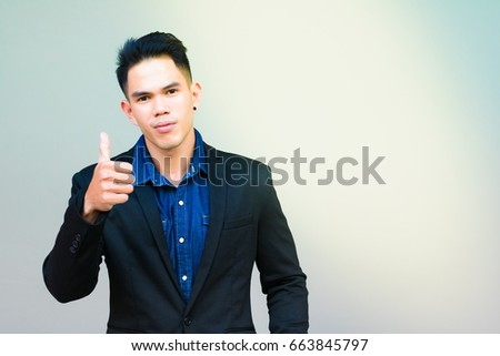 Portrait satisfaction guy: The guy has satisfied some service or some goods or brand by give his thumb up with beautiful sunlight background