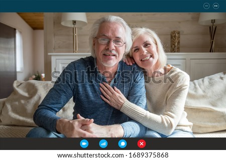 Portrait screen application view of happy mature grandparents sit relax at home have video call with relatives, smiling elderly man and woman talk speak online using Webcam conference on computer