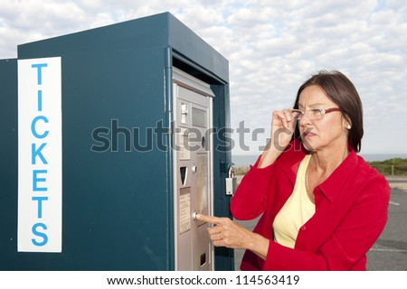 Portrait senior woman at ticket machine outdoor, isolated with blurred background of car park and cloudy sky
