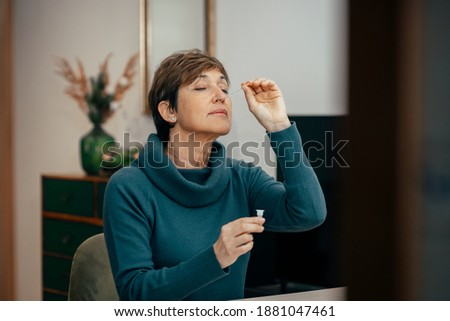 Portrait Senior woman sitting, doing a auto test for COVID-19 at home with Antigen kit. Introducing nasal swab test for possible infection of Coronavirus. Medicine and health-related services online.